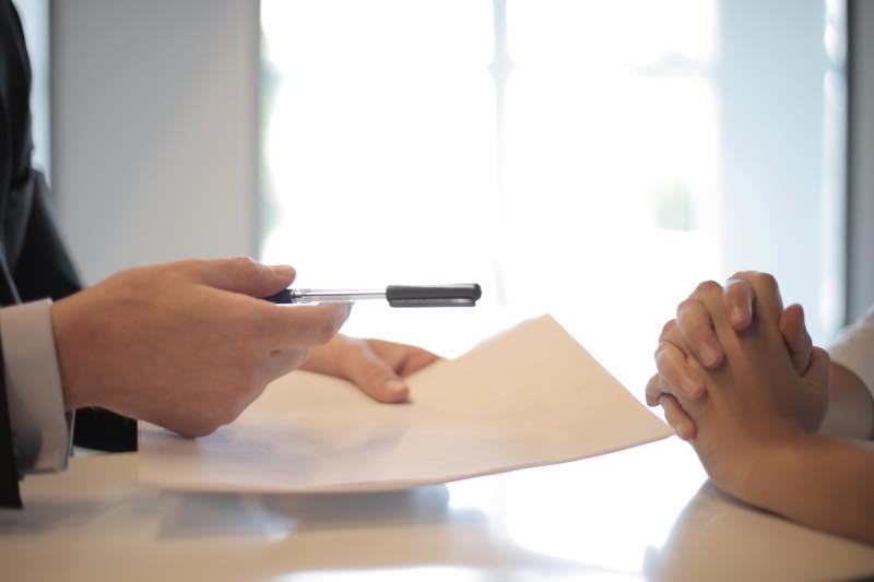 用紙を持って説明する保険セールスマン